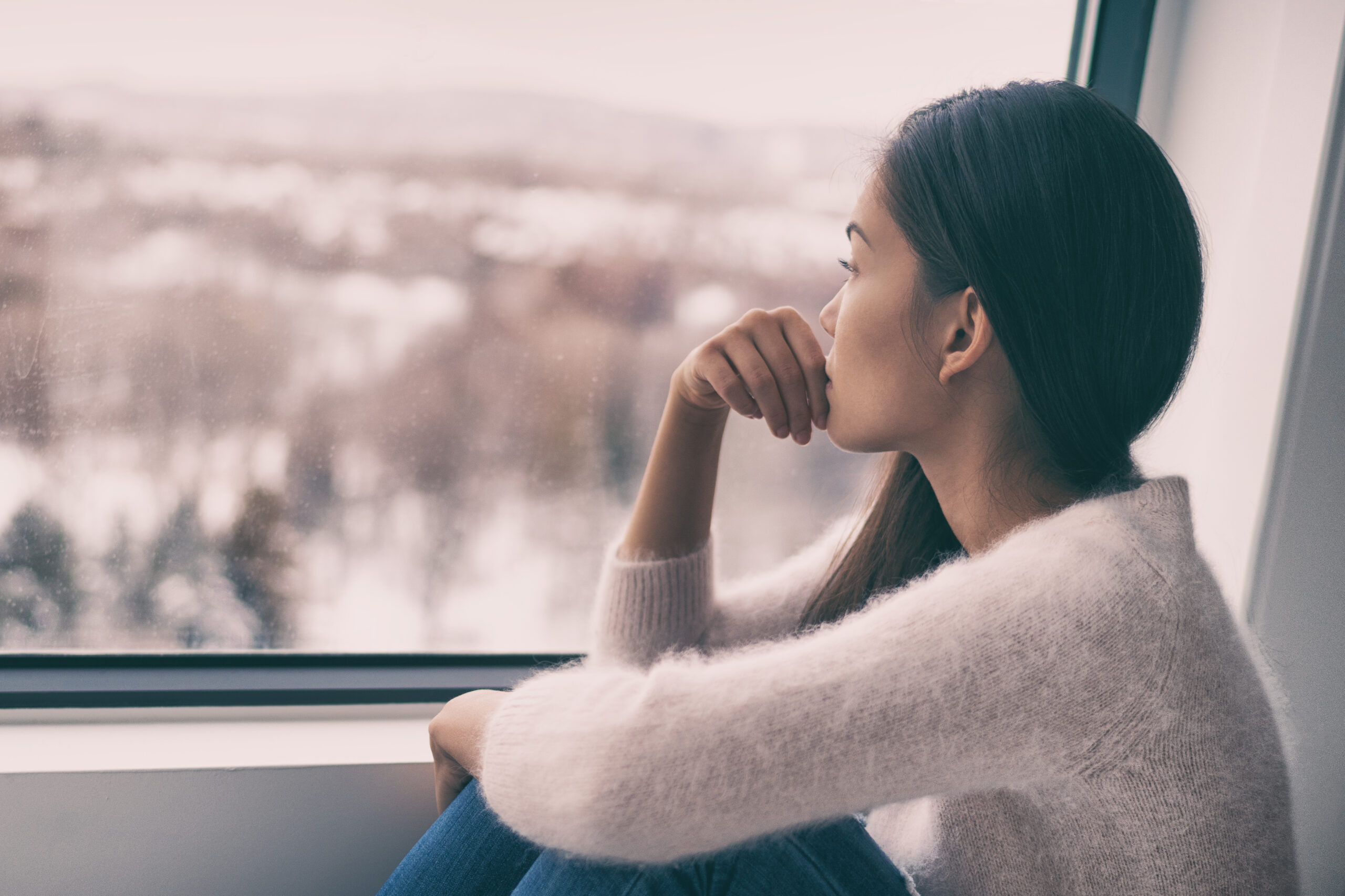 Sad pensive woman at home Winter depression - seasonal affective disorder mental health looking out the window alone. Self isolation